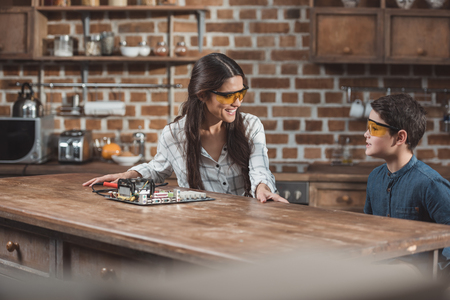 Little son and his beautiful mother wearing protective glasses and working on electronics school project Stock Photo