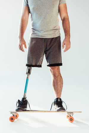 cropped shot of man with leg prosthesis standing on skateboard isolated on white