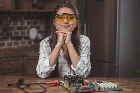 Young woman in protective glasses sitting at table with motherboard on it