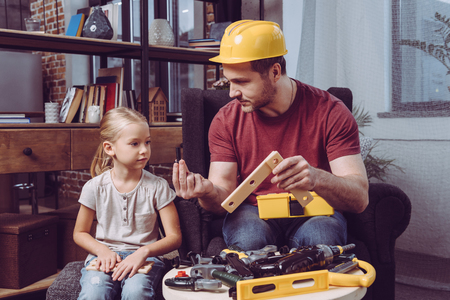 Father showing his daughter how to make a wooden frame with various toy tools at home