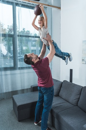Father lifting daughter with american football ball over her head