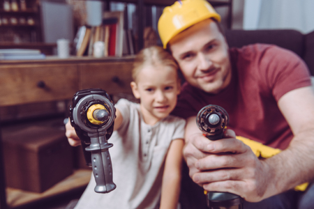 Father and daughter posing with toy drills while making a wooden frame at home