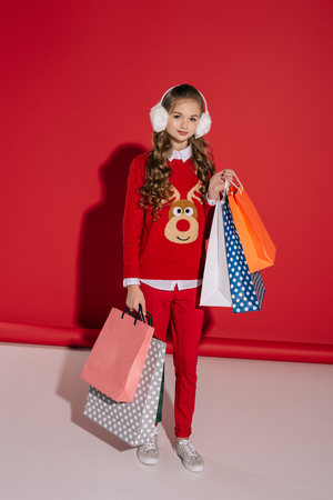 stylish girl in red sweater with reindeer holding shopping bags and smiling at camera  Banco de Imagens