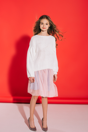 beautiful teenage girl in white sweater and pink skirt smiling at camera on red