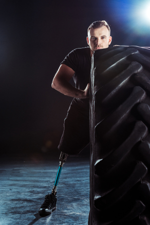 portrait of  sportsman with leg prosthesis pulling tire Stock Photo