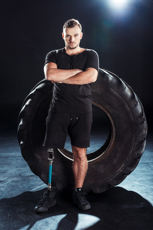 young  sportsman with leg prosthesis and arms crossed leaning on tire Stock Photo