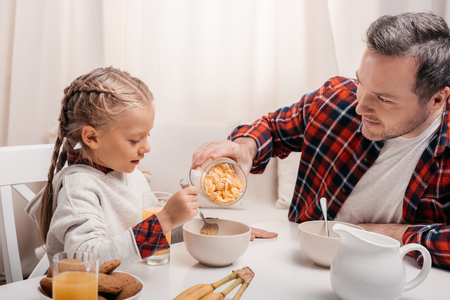 happy father and cute little daughter eating corn flakes at breakfast Imagens