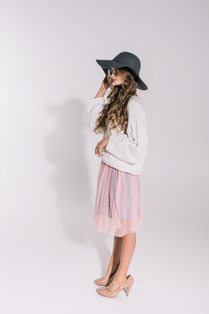 side view of pretty teenage girl in hat and oversized clothes posing isolated on grey Stock Photo