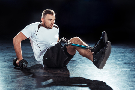 side view of  sportsman with dumbbell doing push ups