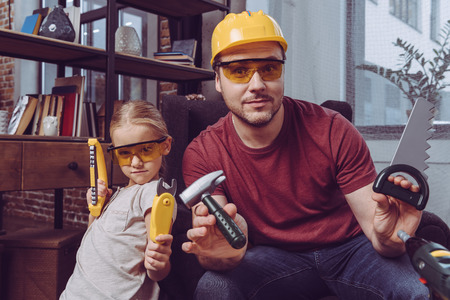 Father and daughter posing with plastic toy tools while making a wooden frame at home