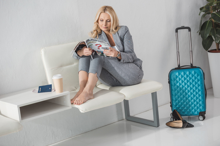 barefoot mature businesswoman reading magazine while waiting for trip
