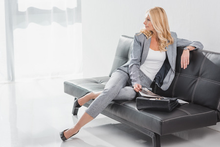mature businesswoman relaxing on couch in office lobby