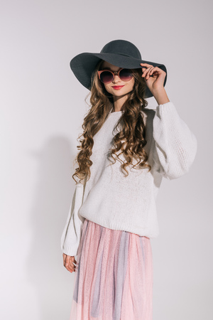 beautiful stylish teenage girl in hat and sunglasses smiling at camera isolated on grey