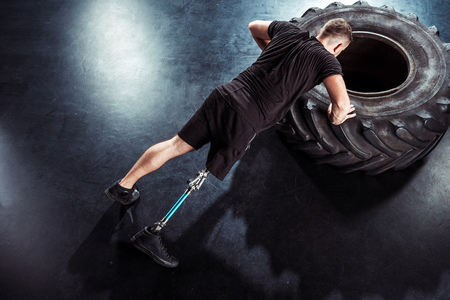 overhead view of  sportsman with leg prosthesis doing push ups on tire Stock Photo