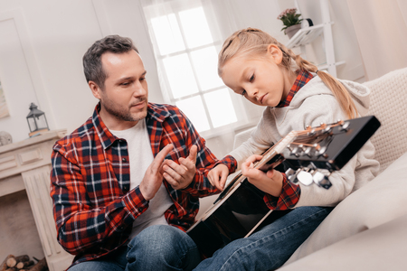 father applauding while cute little daughter playing guitar Standard-Bild - 102642137