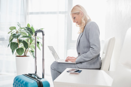 thoughtful businesswoman with luggage using laptop while sitting on chair