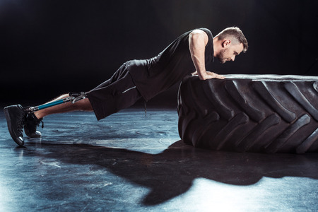 side view of  sportsman with leg prosthesis doing push ups on tire
