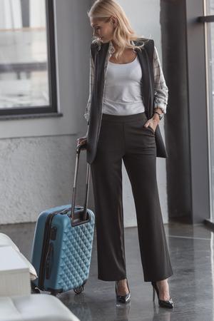 stylish mature woman with suitcase waiting for flight 版權商用圖片