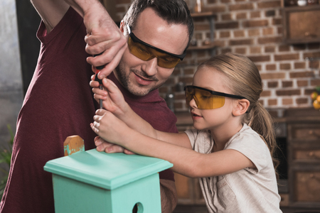 Daughter helping father make birdhouse in the kitchen