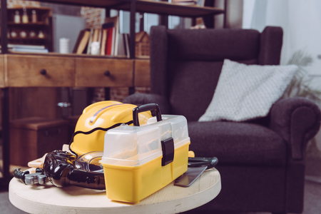 Set of plastic toy tools and yellow toolbox on a table near armchair