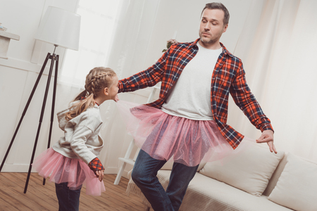 cute little girl laughing and looking at father in pink skirt dancing at home