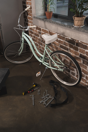 Repaired female bicycle near window at home
