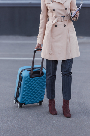 cropped shot of woman in trench coat with luggage Stock Photo