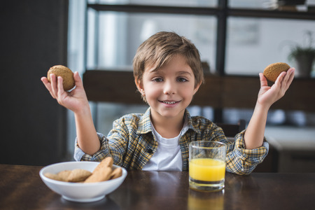 portrait of smiling little boy looking at camera during breakfast at home 免版税图像