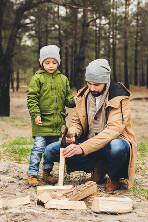 handsome young father and son cutting wood for bonfire in forest