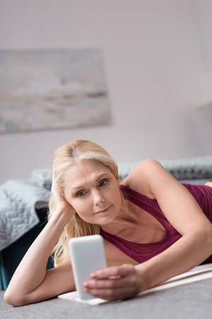 beautiful blonde woman in sportswear using smartphone while lying on yoga mat at home
