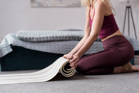 partial view of woman holding yoga mat at home  Stock Photo