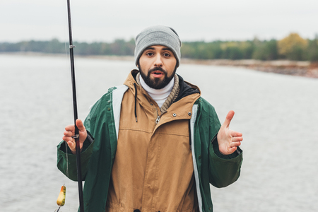handsome man with fishing rod showing size of fish with hands