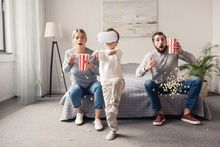 selective focus of parents with popcorn looking at kid playing in vr headset at home