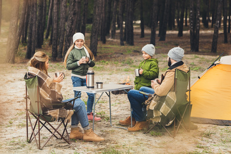 happy family drinking hot tea while having camping trip