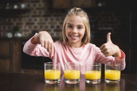 portrait of little cute girl showing thumb up while sitting at table with glasses of juice at home