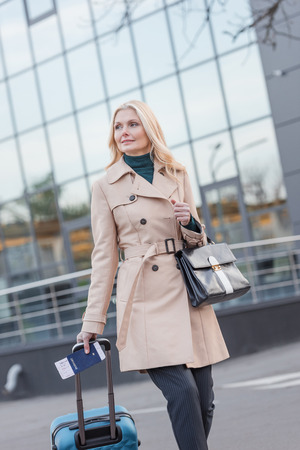 beautiful woman in trench coat with luggage and flight ticket Zdjęcie Seryjne