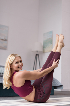 beautiful middle aged woman practicing yoga and smiling at camera at home  Stock Photo