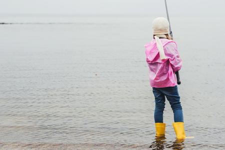back view of lonely little girl fishing in sea