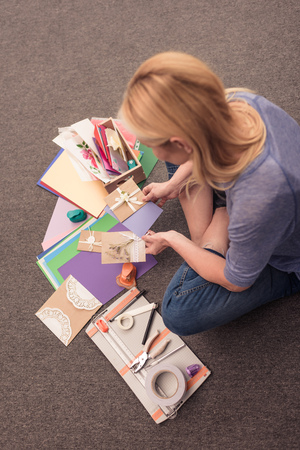 overhead view of blonde woman paper crafting at home