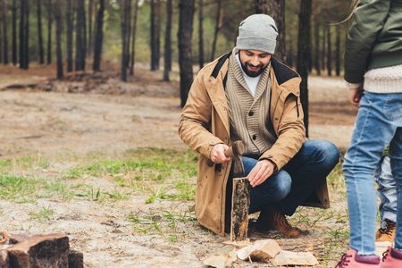 happy young father cutting wood for bonfire while daughter looking at him