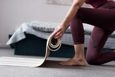 cropped shot of woman holding yoga mat at home  Stock Photo
