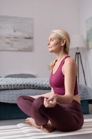 attractive middle aged woman sitting in lotus position on yoga mat at home Stock Photo