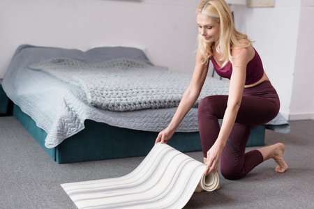 sportive middle aged woman holding yoga mat at home