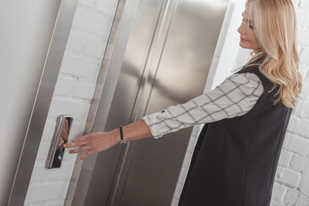 beautiful middle aged woman pressing elevator button Stock Photo