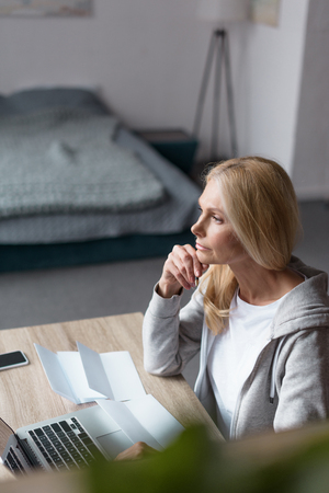 serious middle aged woman looking away while using laptop at home