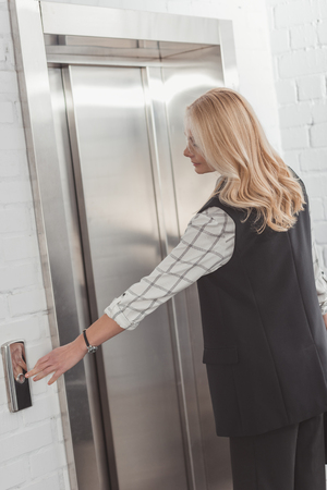stylish middle aged woman pressing elevator button