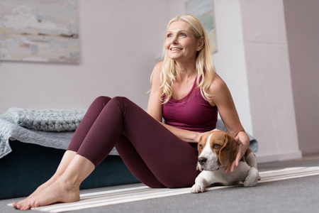 smiling middle aged woman looking away while sitting with dog on yoga mat
