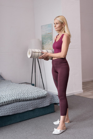 full length view of beautiful sporty middle aged woman holding rolled yoga mat at home Stock Photo