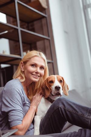beautiful smiling woman stroking beagle dog at home