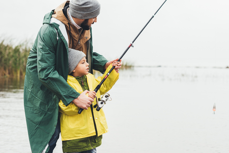 father and son fishing together on cold autumn day